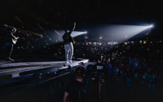 An artist performing in a crowded arena