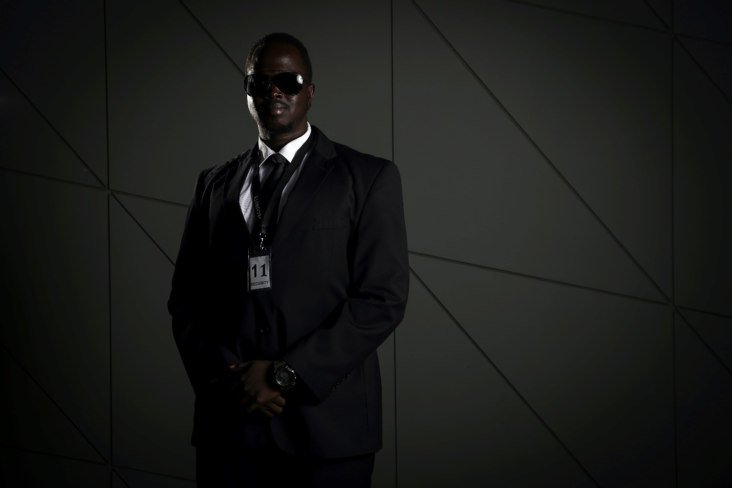 Security guard in a suit standing against a wall